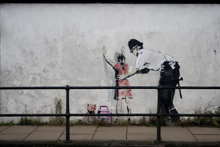 Policeman Searching Girl – Glastonbury Iconic Works by Banksy